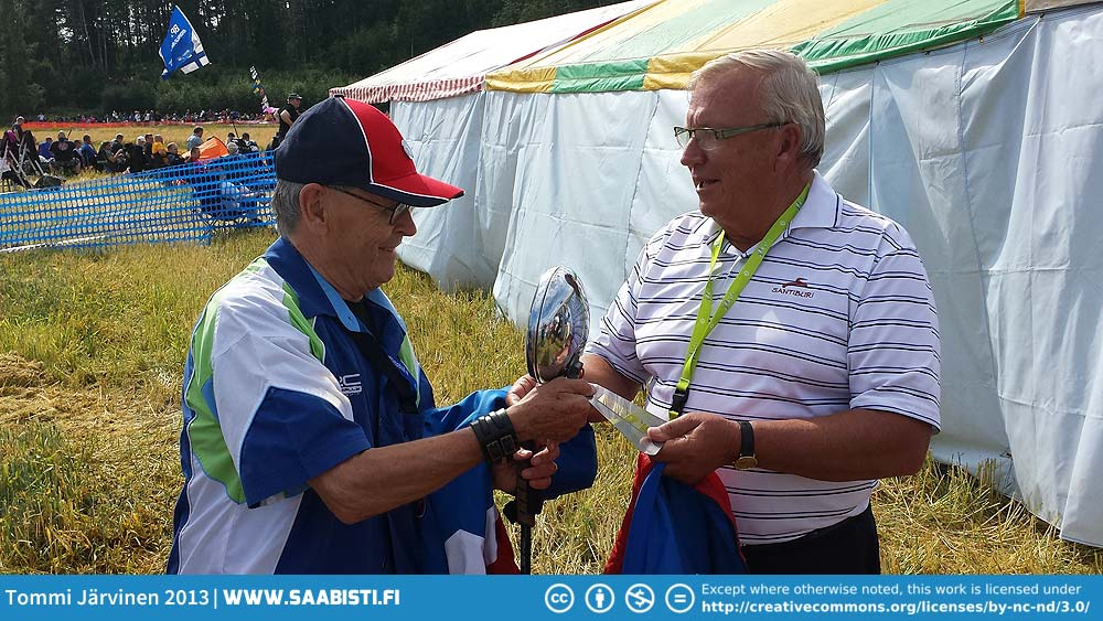 Simo receiving his 70th birthday present - a Bosch ditch light - from his former co-driver Juhani Markkanen.