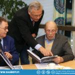 """Vasemmalla Simo Lampinen, Peter Geitel esittelee kirjaa, oikealla Mirja """"Milli"""" Lampinen."""