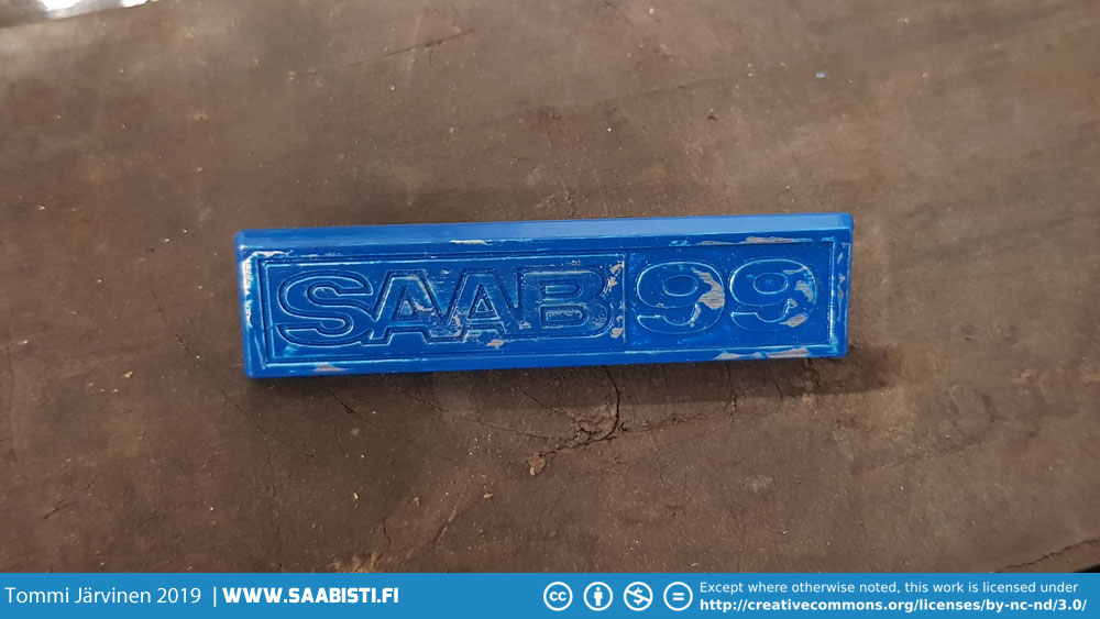 Painting the Saab 99 dashboard emblem blue.